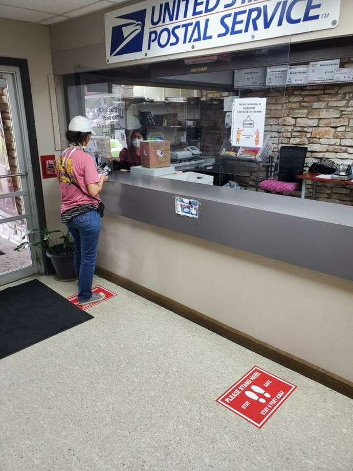 A customer uses the U.S. Post Office window inside Windcrest City Hall. The post office reopened June 1 with physical distancing rules in place. Photo: Photo Courtesy City Of Windcrest