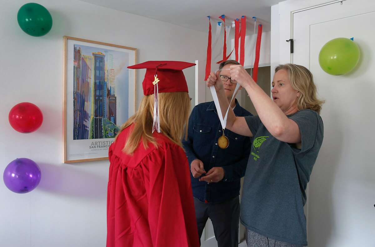 Nettie Atkisson and her husband Curtis help daughter Annie try on a Lowell High class of 2020 graduation gown at their home in San Francisco, Calif. on Wednesday, June 10, 2020. The Atkissons own a duplex and rent their other unit to a tenant.