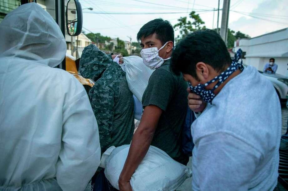 Guatemaltecos deportados por Estados Unidos, usando mascarillas para prevenir el coronavirus, abordan un autobús tras llegar al Aeropuerto La Aurora, en Ciudad de Guatemala, el 9 de junio de 2020. Photo: Moises Castillo /Associated Press / Copyright 2020 The Associated Press. All rights reserved