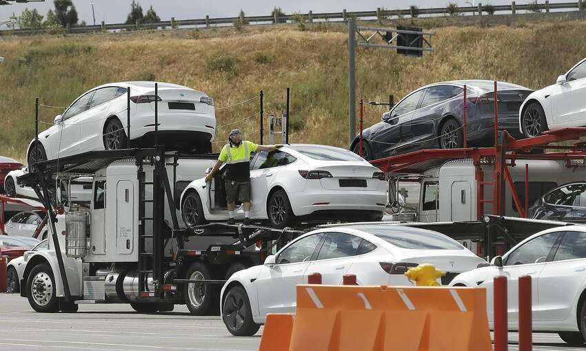 A worker loads a truck with Tesla cars at the Tesla plant Tuesday, May 12, 2020, in Fremont, Calif. Tesla CEO Elon Musk has emerged as a champion of defying stay-home orders intended to stop the coronavirus from spreading. He reopened Tesla's San Francisco Bay Area factory on Monday and President Donald Trump is supporting that decision. (AP Photo/Ben Margot)