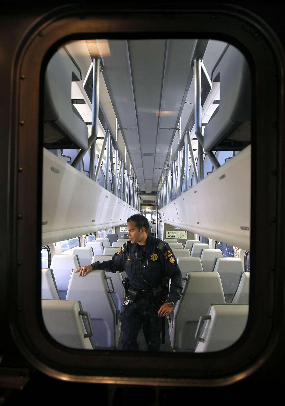 San Mateo County Sheriff's Deputy Brandon Hensel, assigned to the transit patrol detail, walks through an empty train at the Caltrain station in San Francisco, Calif. before it heads southbound on Wednesday, Aug. 8, 2012.