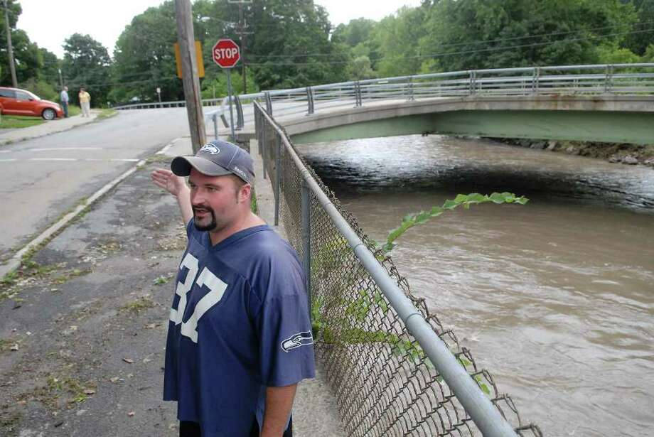 Vic Venette describes seeing a structure that he thinks was a shed crushed against the bridge in the background as the swollen Otsquago Creek carried the structure along on Sunday in Fort Plain.    (Paul Buckowski / Times Union) Photo: Paul Buckowski / 00009955A