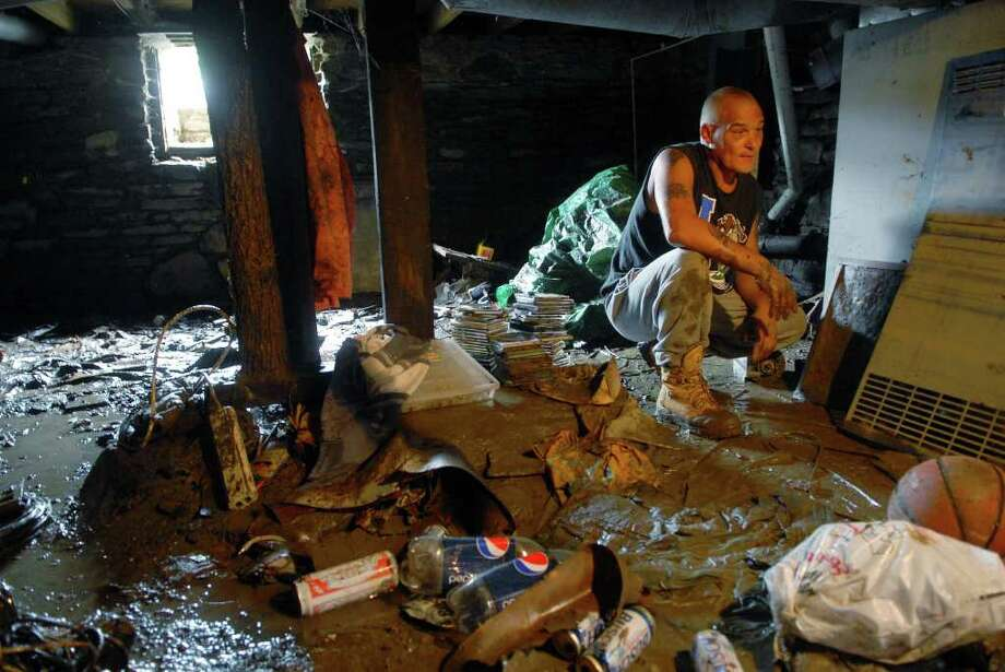 Tim Clemons looks over his belongings, destroyed by Sunday's flooding, in his basement  in Fort Plain on Monday, Aug. 23, 2010.     (Paul Buckowski / Times Union) Photo: Paul Buckowski / 00009955A
