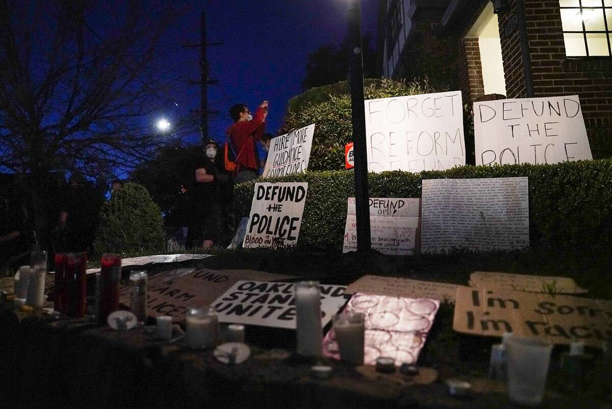 Demonstrators place candles and signs in front of Mayor Libby Schaaf's house during a youth led protest to defund the Oakland Police Department in Oakland, Calif., on Wednesday, June 10, 2020.