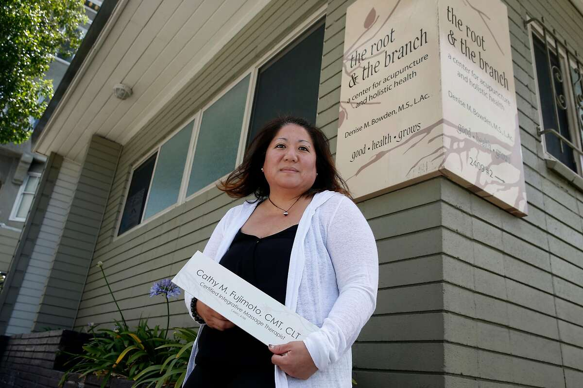 Massage therapist Cathy Fujimoto holds the nameplate that was removed from the studio where she met with clients in San Francisco, Calif. on Wednesday, June 10, 2020. Fujimoto vacated the room she rented for her private practice, which came to a halt three months ago when the coronavirus pandemic led to shelter-in-place orders..