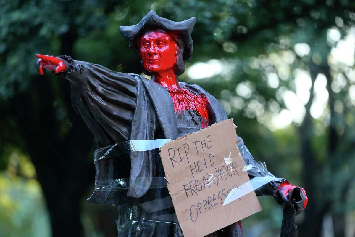 A statue of Christopher Columbus holds a sign and is painted red at Bell Park in Houston on Thursday, June 11, 2020.