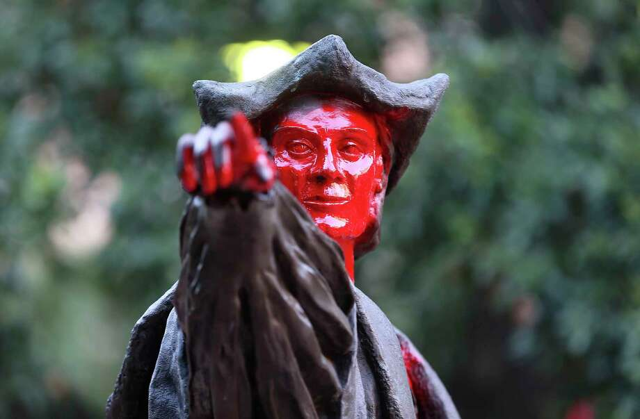 A statue of Christopher Columbus holds a sign and is painted red at Bell Park in  Houston on Thursday, June 11, 2020. Photo: Elizabeth Conley, Staff Photographer / © 2020 Houston Chronicle
