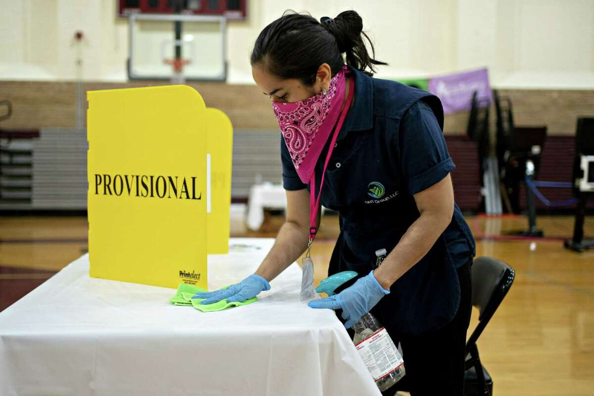 A worker cleans a voting machine booth after being used by a voter at a polling location in Washington, D.C., on June 2, 2020.