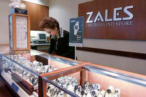 A Zales jewelry store worker looks at watches in San Bruno, Calif.