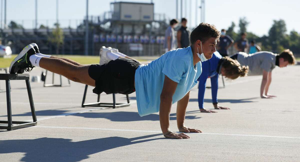 Tristin Kraeter does pushups during a strength and conditioning camp at Grand Oaks High School, Thursday, June 11, 2020, in Spring.