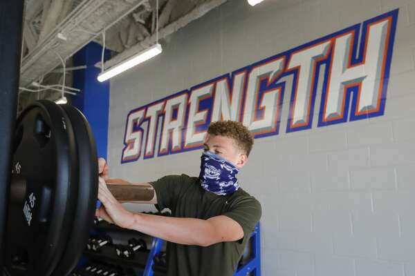 Drew Griffin secures weights during a strength and conditioning camp at Grand Oaks High School, Thursday, June 11, 2020, in Spring.