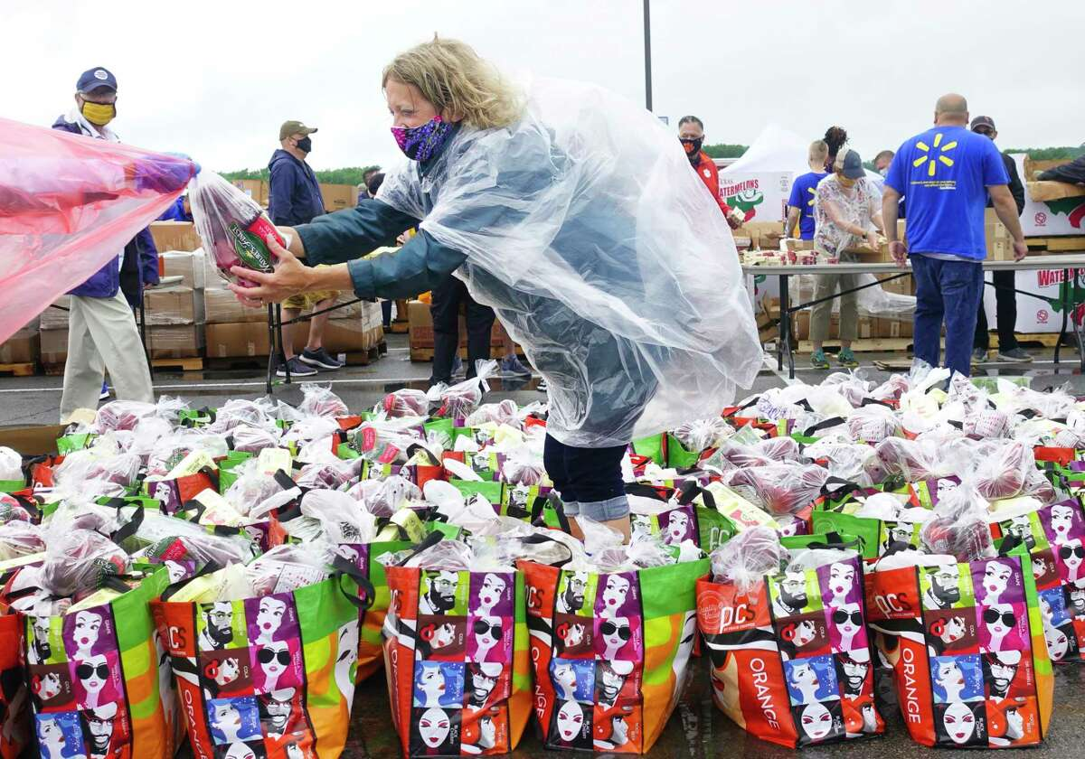 Volunteer, Amy Blanch of Slingerlands, reaches for a bag of apples as she works packing food into bags that will be handed out at the Albany International Airport on Thursday, June 11, 2020, in Colonie, N.Y. The airport, in cooperation with the Regional Food Bank of Northeastern New York, hosted the contactless drive-thru food distribution for anyone in need of food at this time.