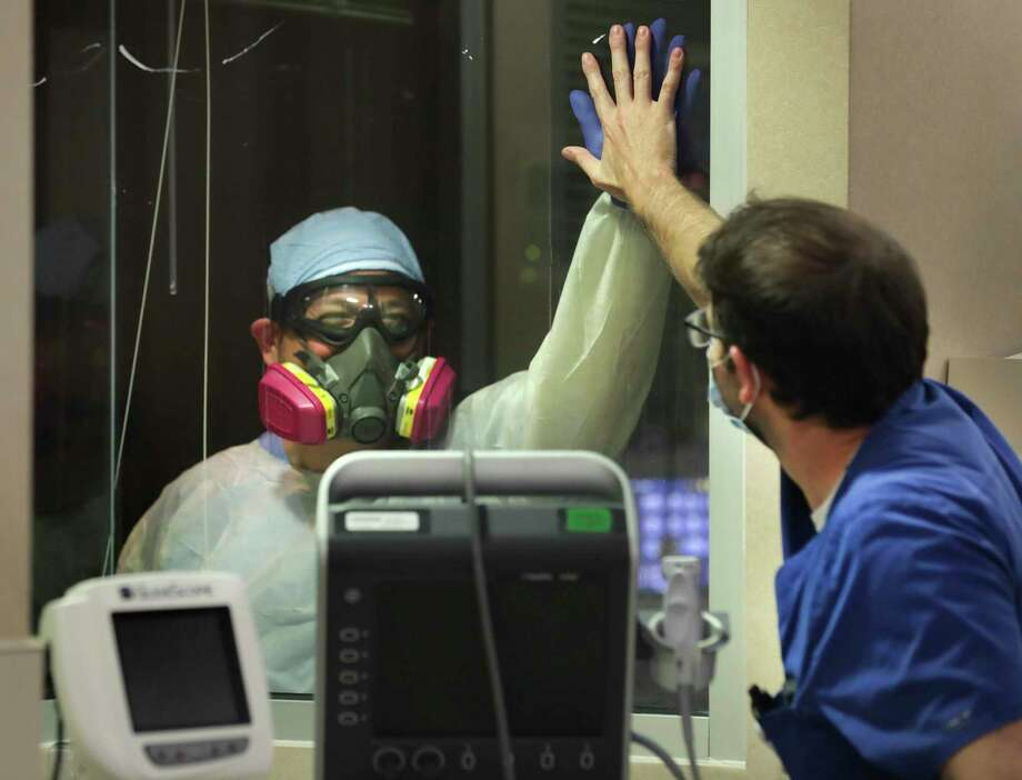 Northeast Baptist Hospital ICU nurse Frank Salinas, left, exchanges a high-five through the glass with overnight charge nurse Sam Beckett after attending to a COVID-19 patient. Photo: Bob Owen / ©2020 San Antonio Express-News