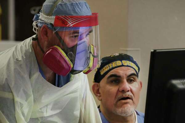 Wearing full protective gear, nurse Simon Denton, left, and Garcia look over information for a COVID-19 ICU patient.