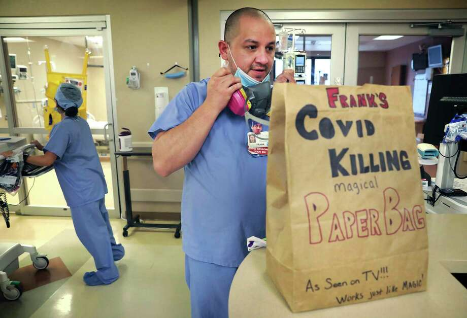 Nurse Frank Salinas puts on his respirator, which he wears while working with patients in the COVID-19 intensive care unit at Northeast Baptist Hospital. The nursing staff store their protective gear in paper bags that several have decorated. Photo: Bob Owen / ©2020 San Antonio Express-News