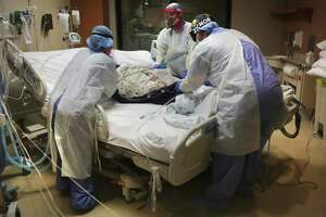 Northeast Baptist Hospital health care workers Lisa Nguyen, left, Simon Denton, center, and Raymond Garcia, move a patient who has been in there more than four weeks to an air mattress in the COVID-19 unit.