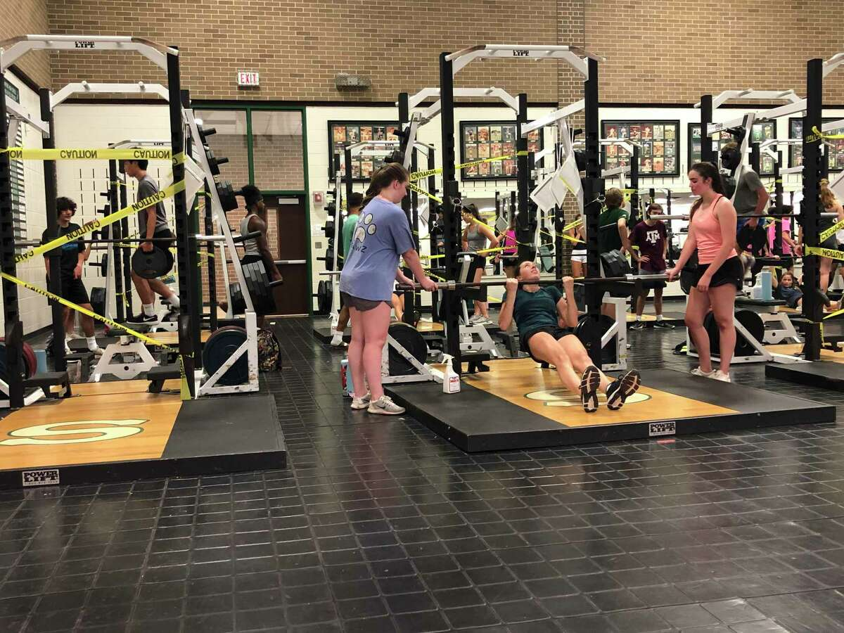 A group of participants at Stratford High School's strength and conditioning camp workout with weights at the school's gym on the morning of June 10. Every other station is taped off to promote social distancing.