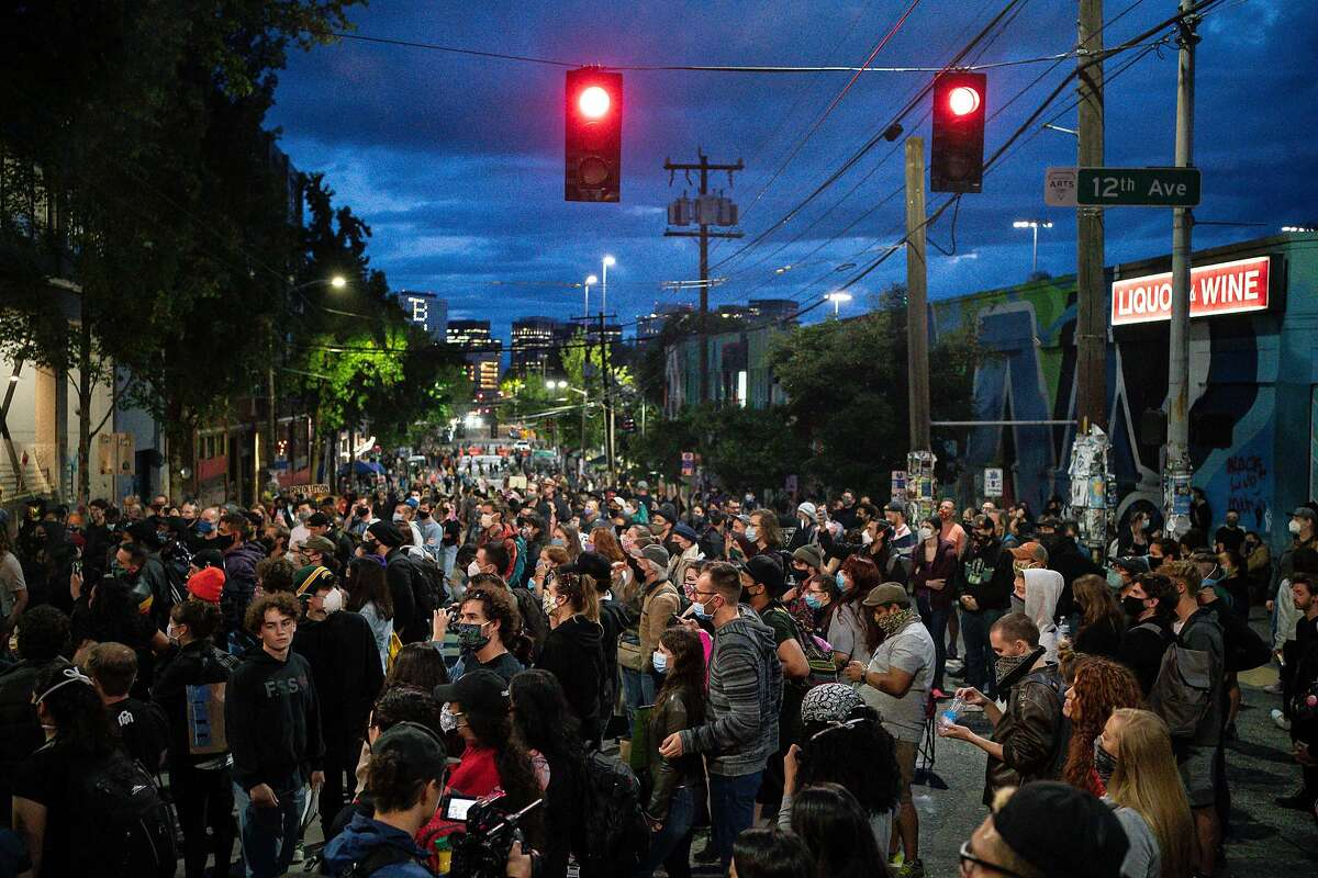 People listen as a band plays a free show in front of the Seattle Police Departments East Precinct in the so-called