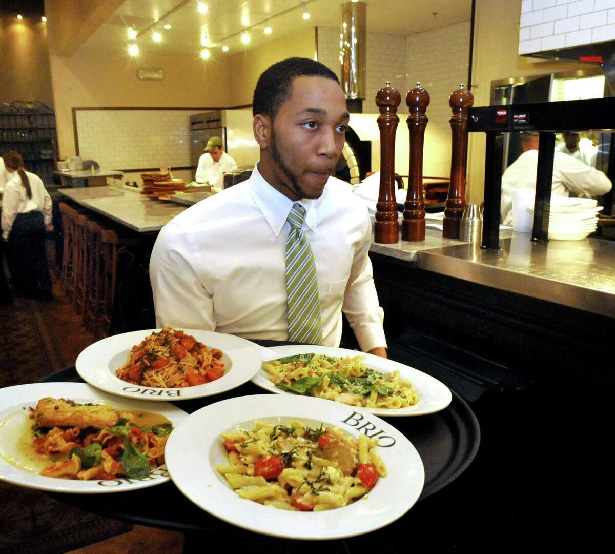 A waiter delivers food in 2012 at Brio at Danbury Fair mall in Danbury, Conn.