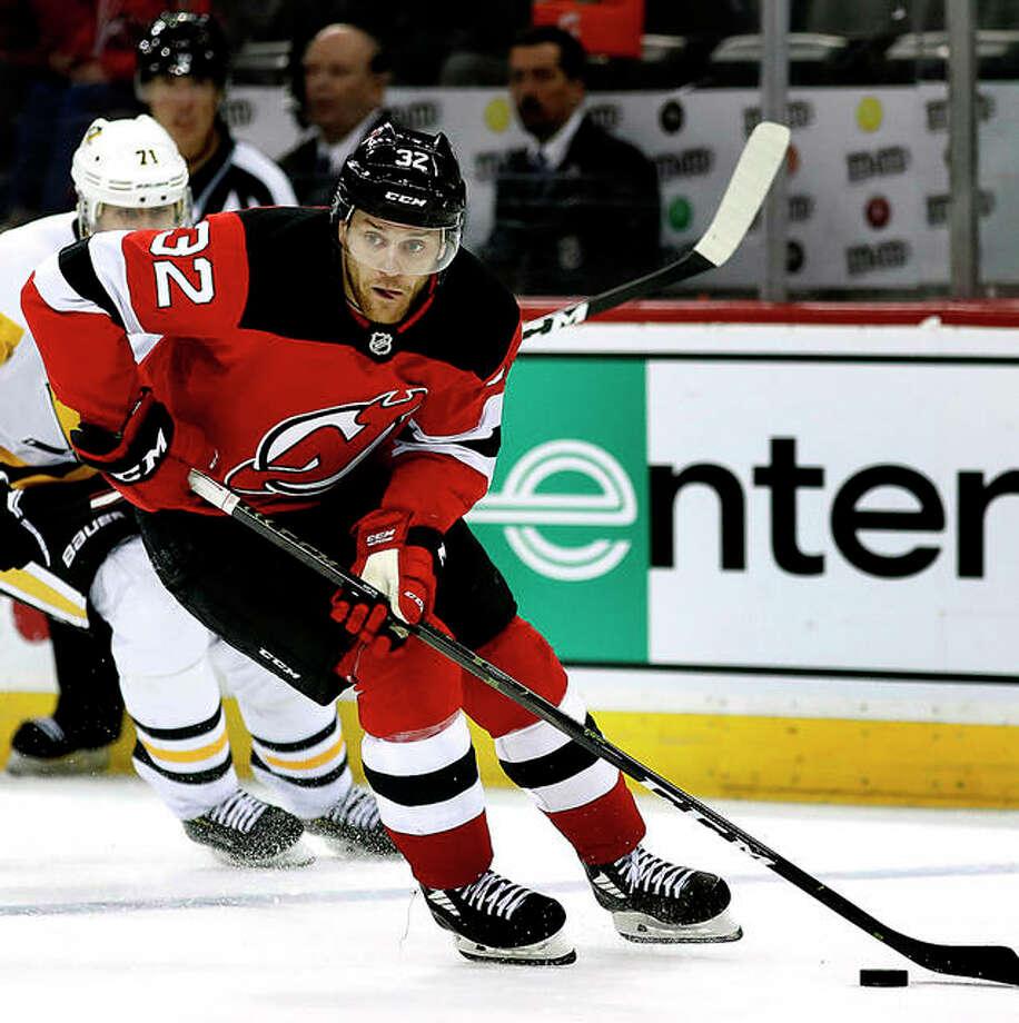 Pittsburgh Penguins center Evgeni Malkin (71) pursues New Jersey Devils defenseman Dakota Mermis (32) March 10 in Newark, N.J. Mrmis is an Alton High graduate and liveds in Gofrey during the offseason.