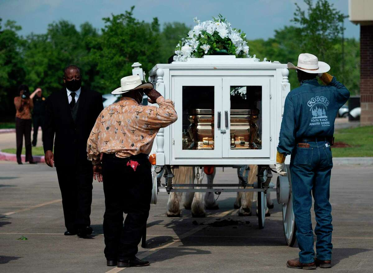 Two cowboys salute the casket of George Floyd after it was loaded onto a white horse-drawn carriage in Pearland to be taken to his final resting place. School and city leaders in Pearland say Floyd's death while in police custody in Minneapolis has sparked them to consider steps to fight racism and promote community dialogue.