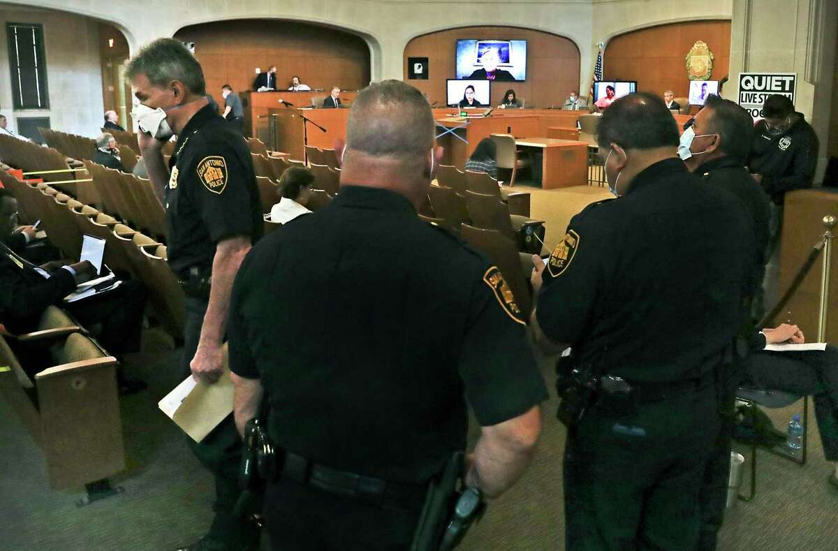 Police Chief William McManus, left, takes a phone call as he and other police officials attend the San Antonio City Council meeting at the Municipal Plaza Building on Thursday, June, 11, 2020.