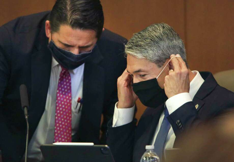 San Antonio Mayor Ron Nerinberg, right, slips on his mask as he listens to City Manager Erik Walsh at a meeting last week. The City Council heard a sobering projection of slow economic recovery and the need for budget cuts at a meeting Thursday. Photo: Bob Owen /San Antonio Express-News / ©2020 San Antonio Express-News