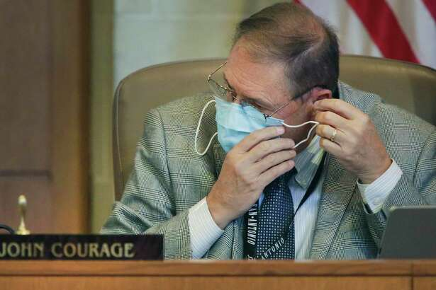 City Council member John Courage puts his mask on at the beginning of the San Antonio City Council meeting at the Municipal Plaza Building on Thursday, June, 11, 2020.