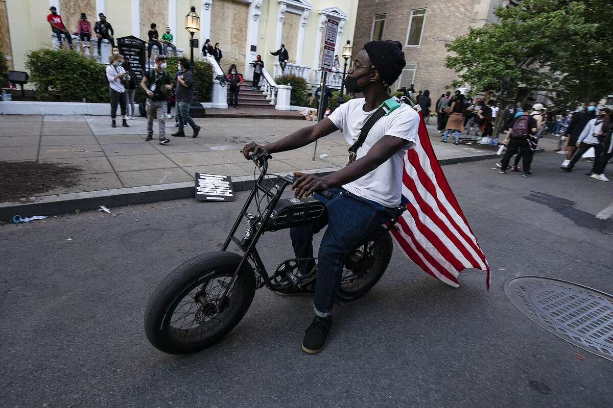 WASHINGTON, DC - JUNE 02: A protestor with an American flag on his back rides a motorized bicycle across the street from the White House during a demonstration over the death of George Floyd, who died in police custody, on June 2, 2020 in Washington, DC. Protests erupted around the country following the release of a video showing Derek Chauvin, a now former Minneapolis Police officer, kneeling on the neck of Floyd despite Floyd saying I cant breath. (Photo by Samuel Corum/Getty Images)
