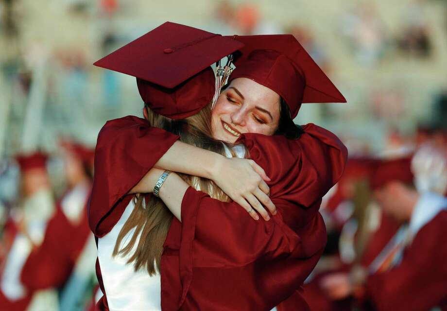 Drew Castleberry gives her sister and Class salutatorian, McKenna, a hug before Magnolia High School's graduation ceremony at Woodforest Bank Stadium, Tuesday, June 9, 2020, in Shenandoah. Photo: Jason Fochtman, Houston Chronicle / Staff Photographer / 2020 © Houston Chronicle