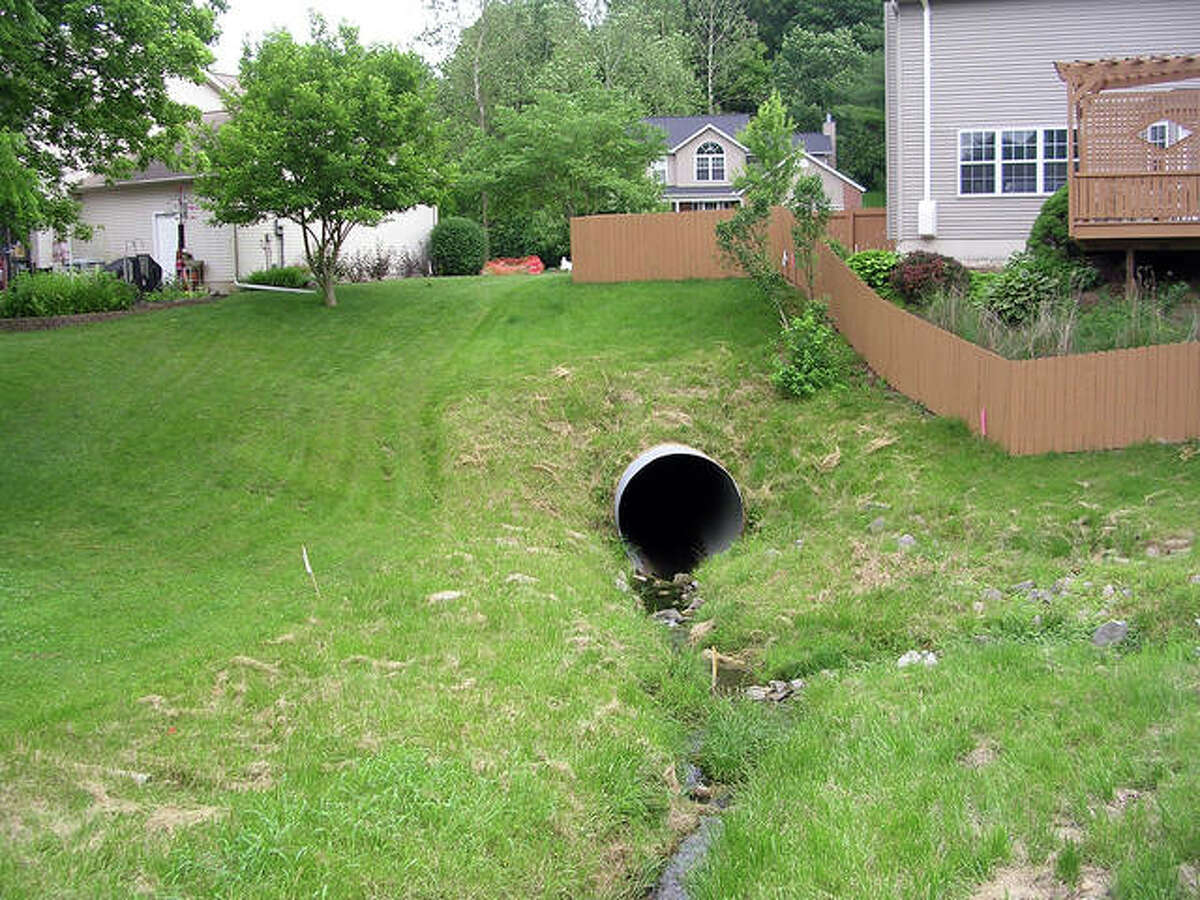 This corrugated metal pipe runs beneath Autumn Glen Drive. Part of the pipe south of here deteriorated last August, causing a sinkhole that has since grown. The view is looking south from the Glen Carbon Public Works access road into the subdivision.