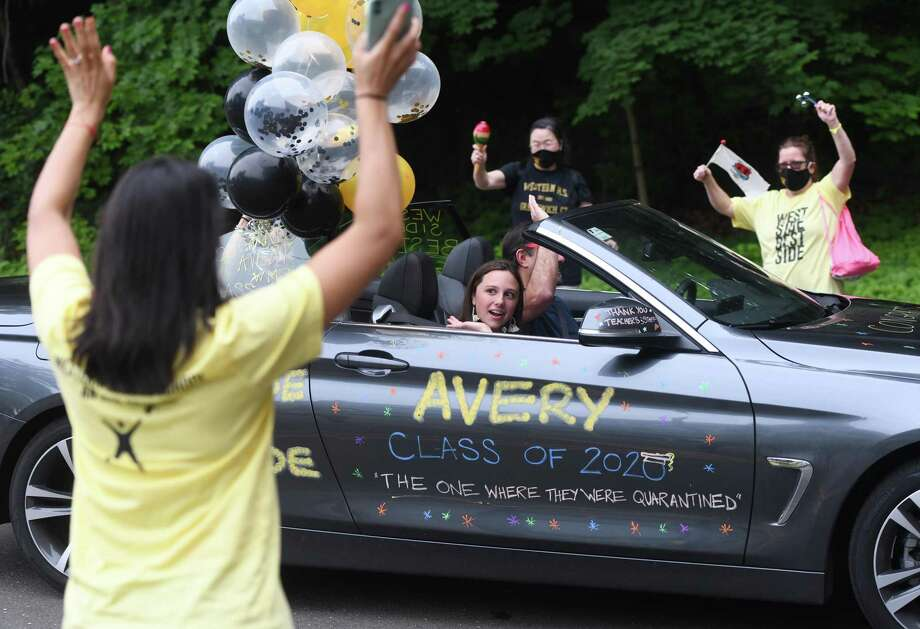 Avery Hirsh waves to her teachers at the drive-thru graduation ceremony at Western Middle School in Greenwich, Conn. Thursday, June 11, 2020. All three Greenwich middle schools held drive-thru ceremonies for their graduating eighth-graders who will head on to Greenwich High School next year. Rows of teachers and faculty cheered as students and their families drove by before taking a photo from inside the car. Photo: Tyler Sizemore / Hearst Connecticut Media / Greenwich Time