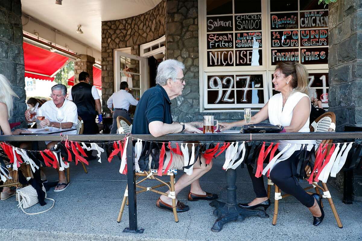 John Kenny and Angelina Preza have drinks at Left Bank Brasserie in Larkspur in June. The French restaurant is reopening for indoor dining now that Marin County has moved into the red tier.