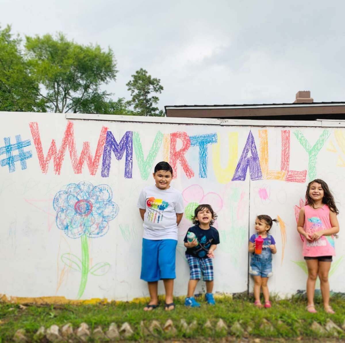 The Lopez family poses under a sign they made for Easter Seals of Greater Houston's virtual Walk With Me fundraiser.