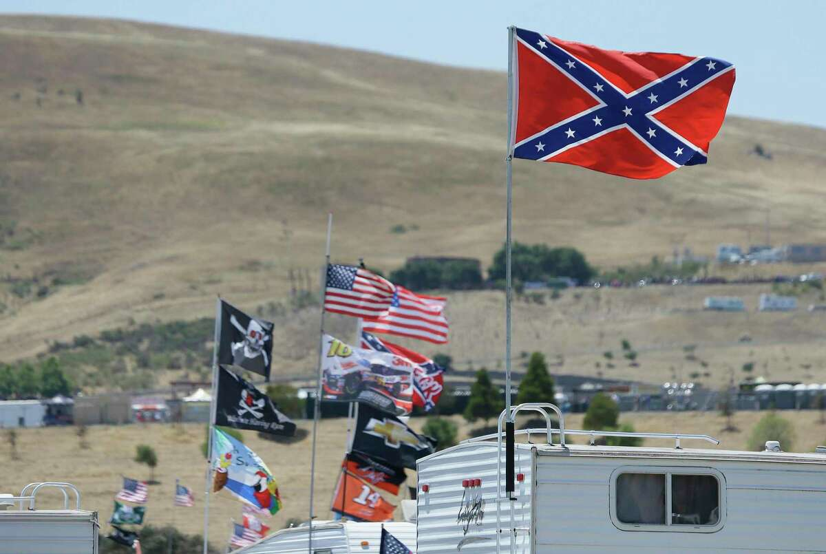 A number of flags, including a couple Confederate-themed ones, fly atop RVs in a campground outside Sonoma Raceway during NASCAR's 2015 stop at the North Bay track.