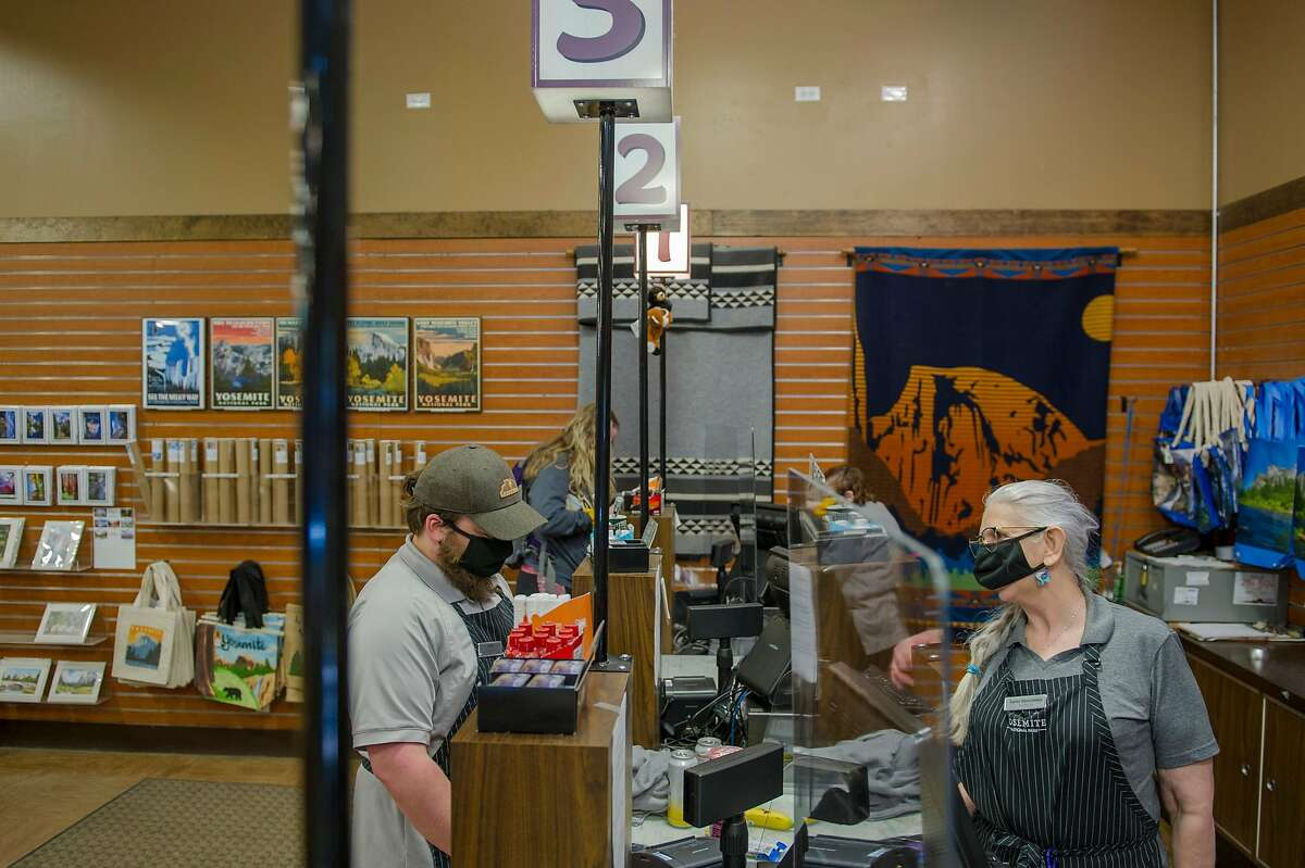 Kevin LeMessurier (left) buys some items from Karen Descoteaux at the Village Store at Yosemite National Park on Thursday, June 11, 2020. LeMessurier and Descoteaux both work at the store.