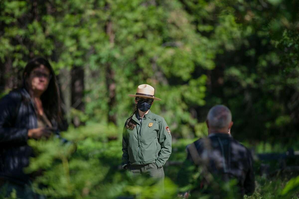 Yosemite park ranger interpreter Jamie Jirele (center) visits with park guests at Yosemite National Park on Thursday, June 11, 2020.