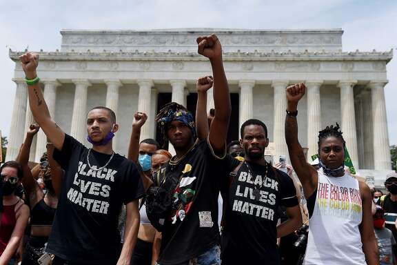 TOPSHOT - Demonstrator raise their fists at the Lincoln Memorial during a protest against police brutality and racism on June 6, 2020 in Washington, DC. - Demonstrations are being held across the US following the death of George Floyd on May 25, 2020, while being arrested in Minneapolis, Minnesota. (Photo by Olivier DOULIERY / AFP) (Photo by OLIVIER DOULIERY/AFP via Getty Images)