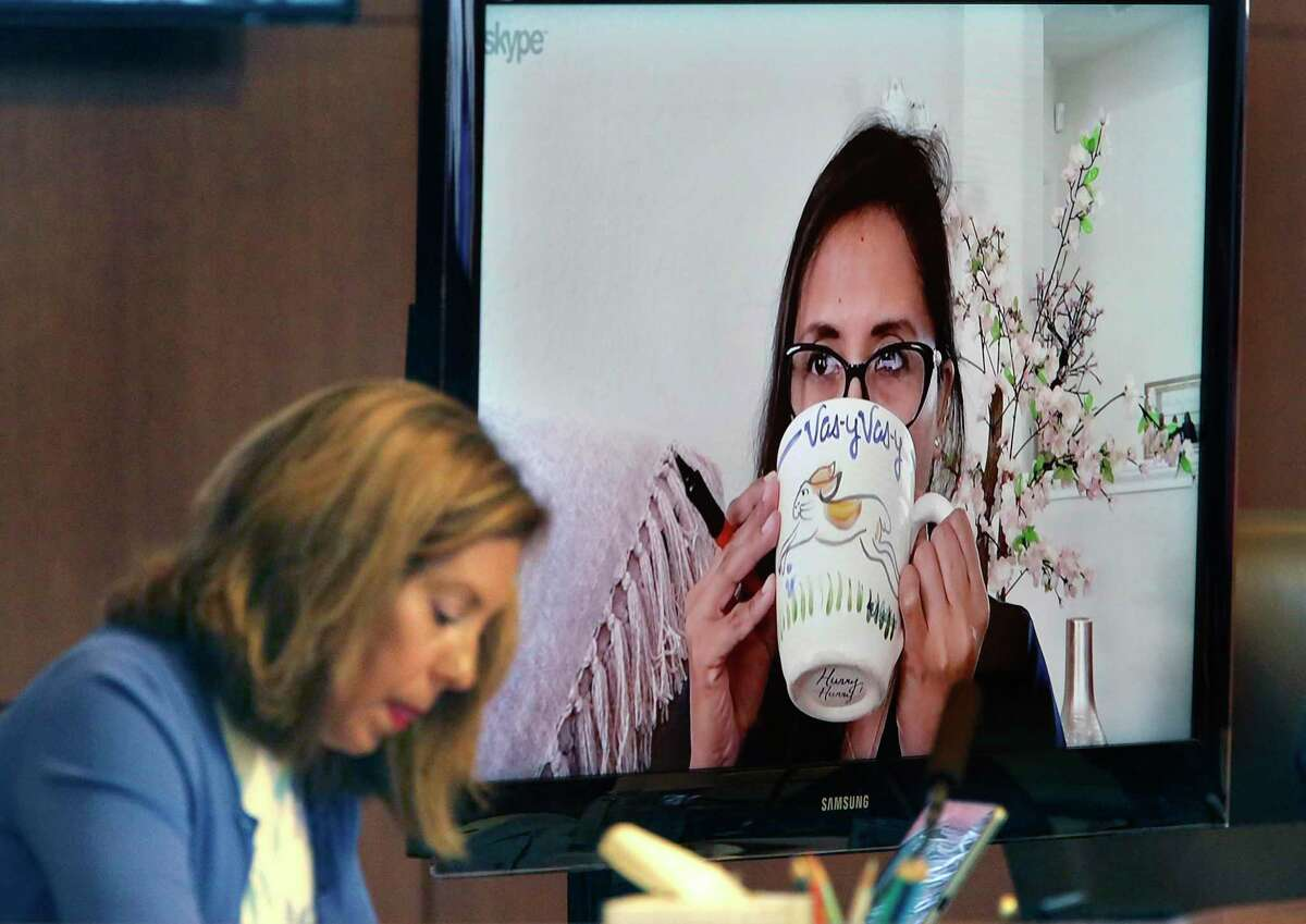 District 4 Council Member Adriana Rocha Garcia, right, takes a sit of coffee at home as she attends the San Antonio City Council meeting via teleconference, at the Municipal Plaza Building, on Thursday, June 11. At left is Council Member Shirley Gonzales of District 5. The council will meet in person Thursday for the first time since June because of the pandemic.