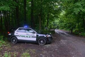 A New Milford police cruiser sits at the entrance to a parking area off Route 7 in Kent for the First Light Bulls Bridge Recreation Area. After hours of searching the day before, dive teams and first responders were back out scouring the river Thursday for the 21- and 24-year-old New York men, who went missing Wednesday while swimming in the Housatonic River. June 11, 2020, in Kent, Conn.