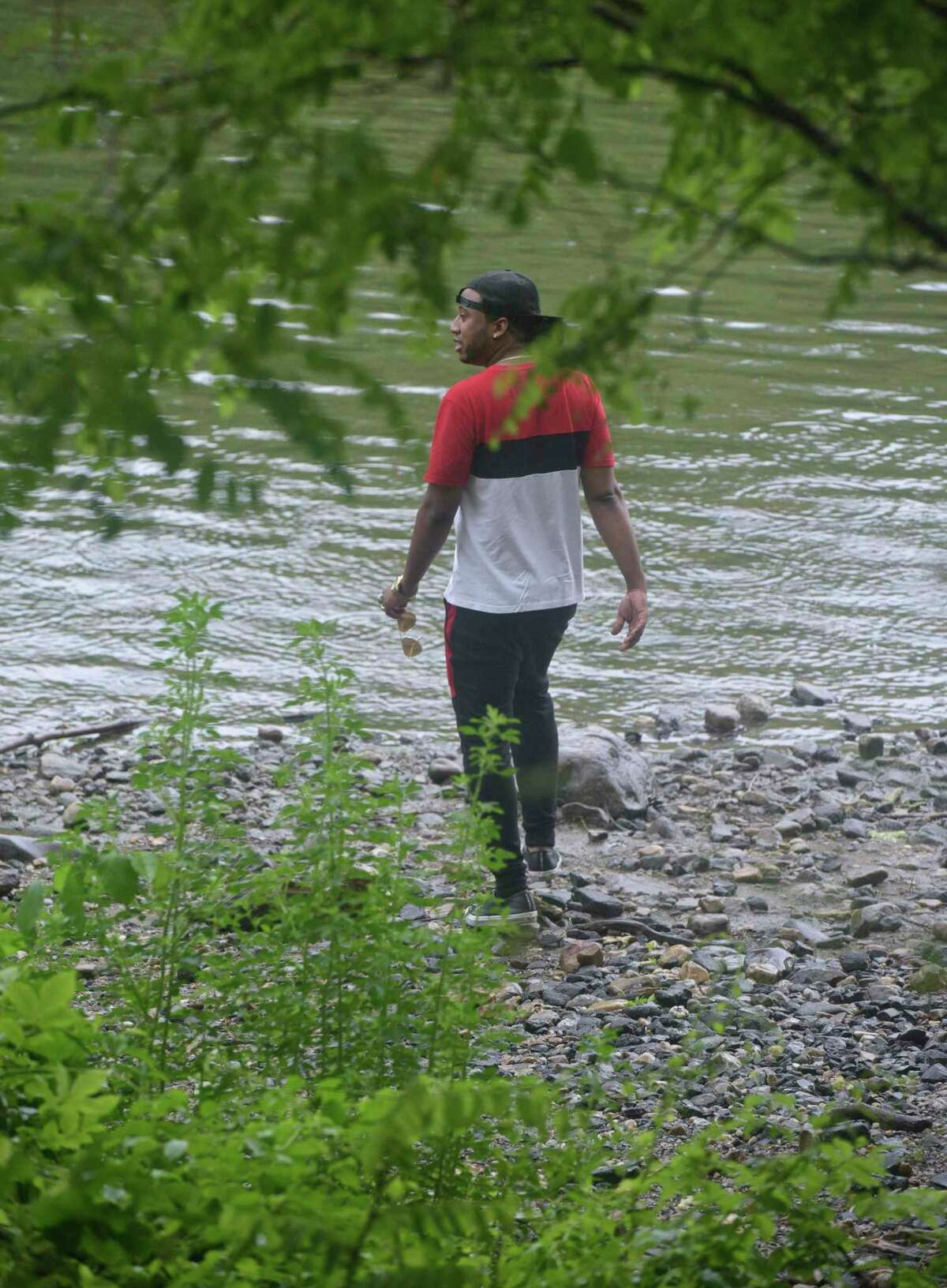 Jonathan Diaz, of New Jersey, stands next to the Housatonic River trying to get a sense of what happened to his cousin who is one of two men who went missing while swimming in the river on Wednesday. After hours of searching the day before, dive teams and first responders were back out scouring the river Thursday for the 21- and 24-year-old New York men, who went missing on Wednesday. June 11, 2020, in New Milford, Conn.