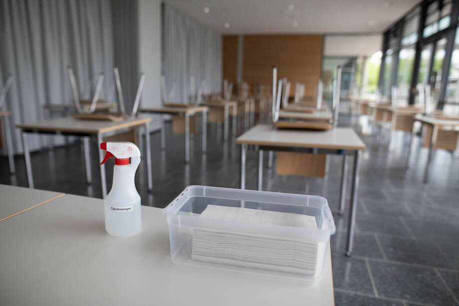 10 June 2020, Baden-Wuerttemberg, Bad Krozingen: A spray bottle with table cleaner and a bowl with paper towels are standing on a desk in a classroom of the upper school in the Kreisgymnasium in Bad Krozingen. Next Monday, June 15th, the schools will again begin a large scale of attendance lessons. To this end, measures have been taken in the schools to prevent infection. Photo: Philipp von Ditfurth/dpa (Photo by Philipp von Ditfurth/picture alliance via Getty Images) Photo: Picture Alliance/dpa/picture Alliance Via Getty I / (c) Copyright 2020, dpa (www.dpa.de). Alle Rechte vorbehalten