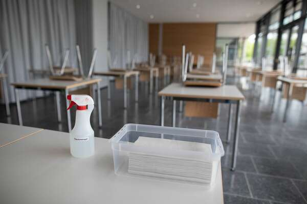10 June 2020, Baden-Wuerttemberg, Bad Krozingen: A spray bottle with table cleaner and a bowl with paper towels are standing on a desk in a classroom of the upper school in the Kreisgymnasium in Bad Krozingen. Next Monday, June 15th, the schools will again begin a large scale of attendance lessons. To this end, measures have been taken in the schools to prevent infection. Photo: Philipp von Ditfurth/dpa (Photo by Philipp von Ditfurth/picture alliance via Getty Images)