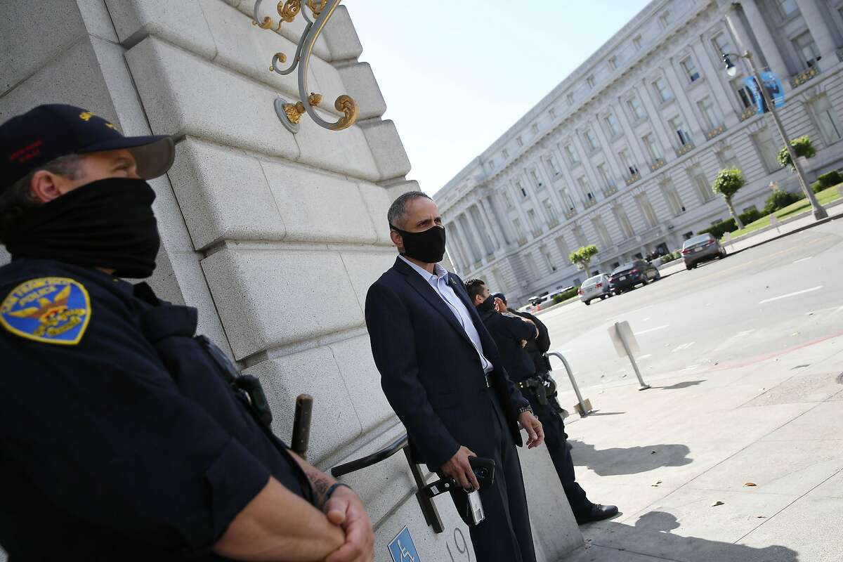 Tom�s Aragon, director Population Health Division; Health Officer; City and County of San Francisco; walks out of the Department of Public Health as officers stand next to the building as they monitor a Black Lives Matter protest on Friday, June 5, 2020 in San Francisco, Calif.