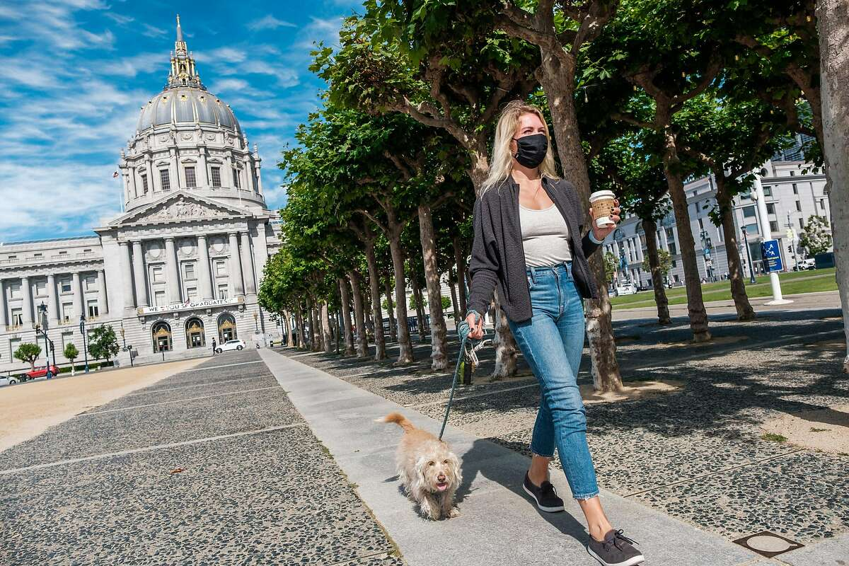 Brittany Casciotti, who was recently laid off from her job as a producer at KPIX, walks with her dog. Charlie, in San Francisco on Thursday, June 11, 2020.