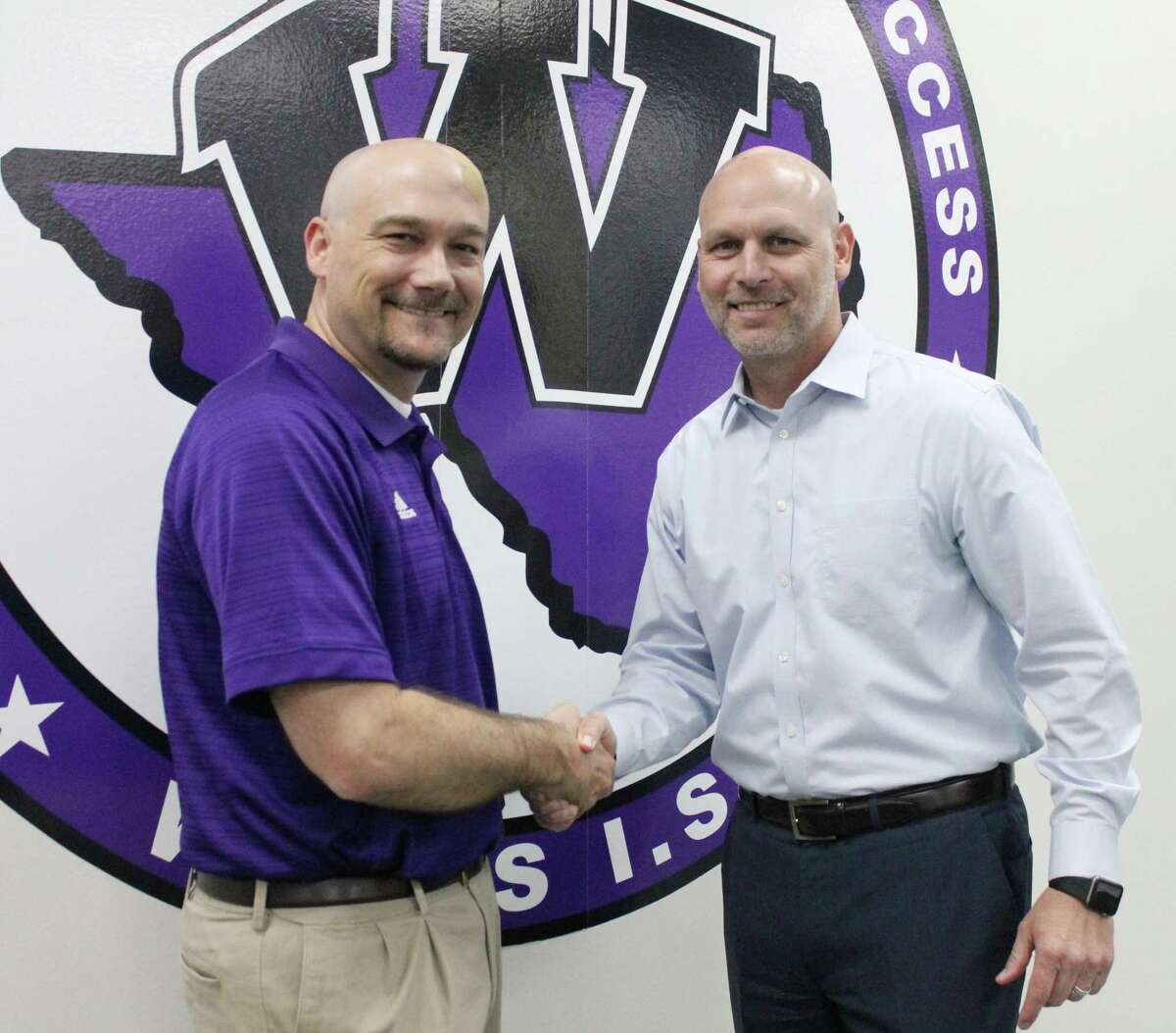 Willis ISD Superintendent Tim Harkrider shakes hands with Dr. Brian Greeney when the district named him as the new assistant superintendent in 2017.