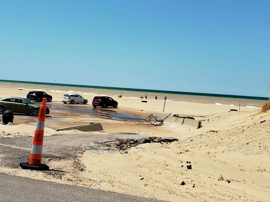 Recent wind storms have shifted sands at First Street Beach where a previous driveway was uncovered to reveal crumbling asphalt underneath. The area was blocked off with cones in this Thursday photo. (Arielle Breen/News Advocate)