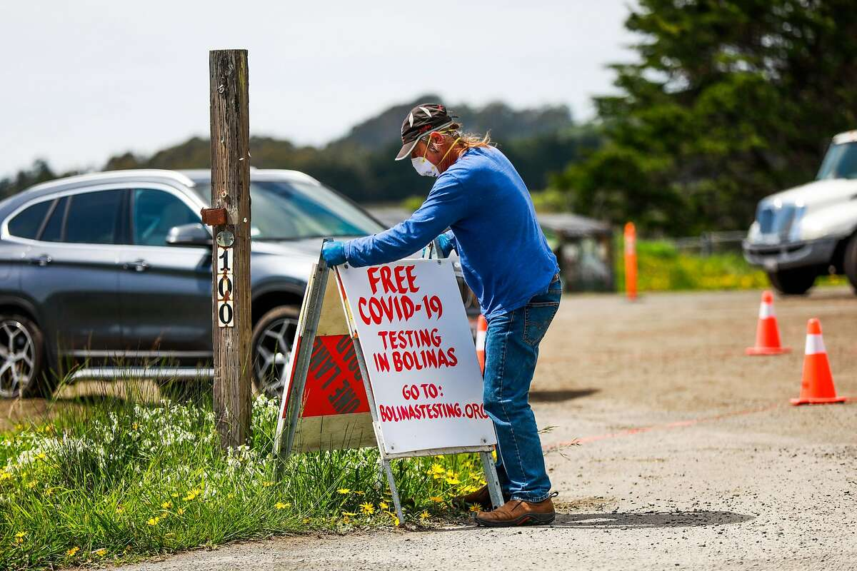 Charles Whitefield puts out a sign for a covid-19 testing site in Bolinas, California on Sunday, April 19, 2020.