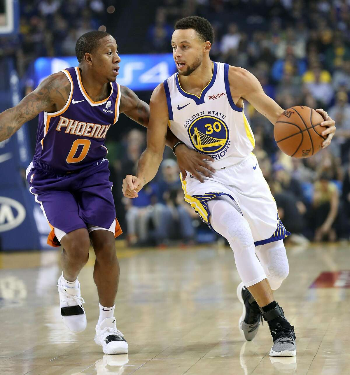Golden State Warriors' Stephen Curry is guarded by Phoenix Suns' Isaiah Canaan during NBA game at Oracle Arena in Oakland, Calif.. on Monday, October 22, 2018.