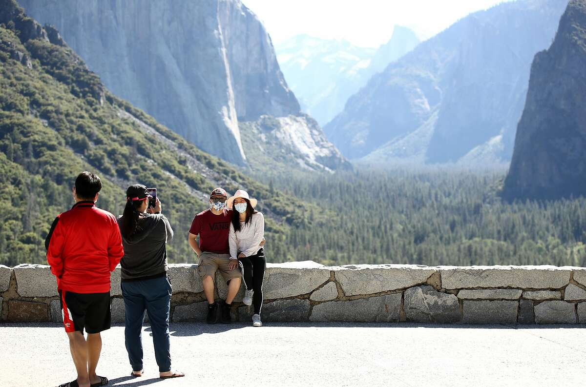 Visitors, wearing masks for safety, take pictures at the Tunnel View lookout.